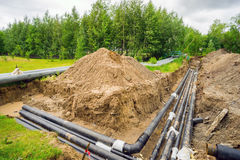 New heating pipeline in the excavated trench on town. royalty free stock photos