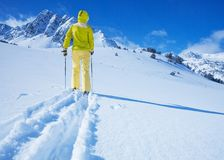 New heights pioneer. One man walking with ski over the snow land to the mountain view from back Stock Photo