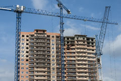 A new high-rise building and three construction cranes. New monolith-brick house surrounded by construction cranes Royalty Free Stock Photo