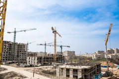 New high-rise houses and column crane. New multistorey building and industrial construction cranes. tower and mobile cranes on construction site Stock Photography