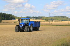New Holland Tractor and Blue Trailer Autumn Field Landscape. SOMERO, FINLAND - SEPTEMBER 12, 2015: New Holland T7.250 Tractor and blue agricultural trailer on Royalty Free Stock Photo
