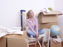 New Home. Happy woman with boxes just moving into her new home Royalty Free Stock Image