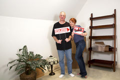 New Home Sale. Man and woman standing in their new home holding real estate signs Stock Images