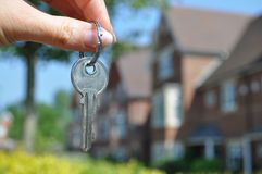New home. Female hand holding a key to a house Royalty Free Stock Photo