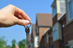 New home. Female hand holding a key to a house Stock Photos