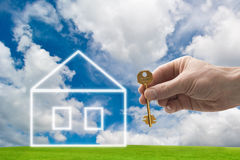 New home. Hand holding a house key with a new home Stock Image