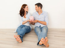 New home. Happy parents dreaming new home with piggy bank for money Stock Photo