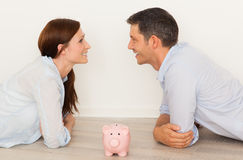 New home. Happy parents dreaming new home with piggy bank for money Stock Image