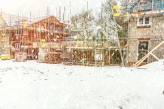 New Home Building. Construction site building a new brick home during winter time, snowing conditions royalty free stock image