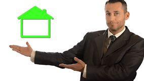 A new home. A businessman and a green miniature house. Royalty Free Stock Images