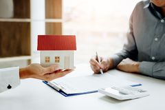 New home buyer signing contract with agents are holding the mode. L house royalty free stock photo