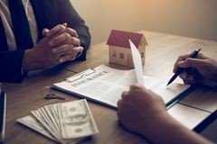 New home buyers are signing a home purchase contract at the agent`s desk.  stock photography