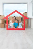 New home concept. With happy people among cardboard boxes holding house shaped frame Stock Photography
