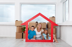 New home concept with woman and kids. New home concept with women and kids and lots of cardboard boxes in empty room Royalty Free Stock Photo