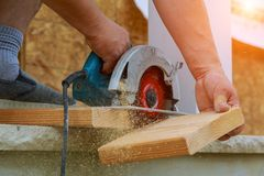 Building contractor worker using hand held worm drive circular saw to cut boards on a new home constructiion project royalty free stock photography