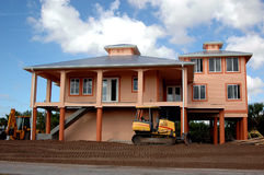 New home construction. A new home built high in a flood zone with a bulldozer out front and another on the side Royalty Free Stock Photos