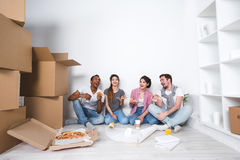 New home. Friends sitting on the floor in the new apartment and eating pizza after unpacking. royalty free stock images