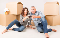 New home. Happy couple celebrating their new home, vine glasses in hands Stock Images