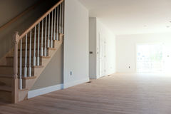 New Home Interior Stairs. New home construction interior room with unfinished wood floors stairway and railings. Electrical and hvac connections also are Stock Image