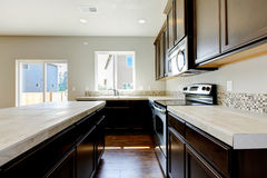 New home kitchen interior with dark brown cabinets. New home kitchen interior with dark brown cabinets and hardwood floors Stock Photo