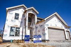 New home partially finished, under construction in residential housing subdivision with for sale sign in yard stock images