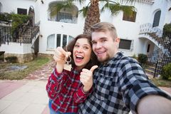 New Home, real estate and moving concept - Funny young couple showings keys from new house. New Home, real estate and moving concept - Funny young couple royalty free stock photography