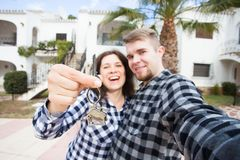 New Home, real estate and moving concept - Funny young couple showings keys from new house. New Home, real estate and moving concept - Funny young couple stock photo