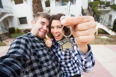 New Home, real estate and moving concept - Funny young couple showings keys from new house. New Home, real estate and moving concept - Funny young couple royalty free stock image