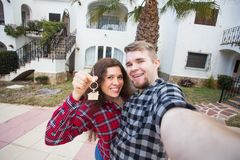 New Home, real estate and moving concept - Funny young couple showings keys from new house. New Home, real estate and moving concept - Funny young couple royalty free stock photos
