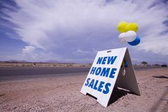 New home sales. New home sale sign near highway Royalty Free Stock Photo