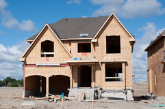 New Home Under Construction. A new home under construction with blue sky and clouds Stock Image