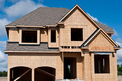 New Home Under Construction. A new home under construction with blue sky and clouds Stock Photo