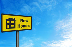 'New Homes' photo realistic sign. Against a blue sky, with space for your text / editorial overlay Stock Images