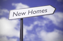 New homes. Road sign against a blue sky stock images