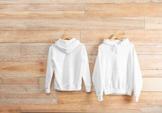 New hoodie sweaters with hangers on wooden wall. Mockup for design stock image