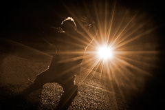 New Hope. Man facing the strong light on his knees royalty free stock photo