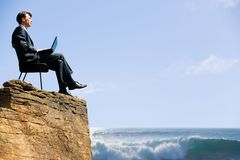 New horizons. Image of confident business man sitting on the top of rock with laptop and looking at sea below Stock Image