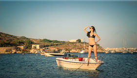 New horizons. Beautiful woman standing on a little boat in the water looking in the distance royalty free stock images