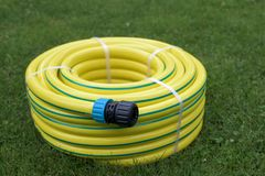 New hose pipe. New yellow hose pipe in a garden royalty free stock photos