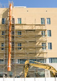 New hospital under construction. Scaffolding and earth mover beside hospital under construction stock image