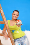 New house. Young repair woman offering a miniature house to us Royalty Free Stock Images