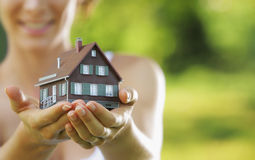 New house. Young beautiful woman offering a house Royalty Free Stock Photo