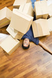 New house. High angle view of young man sleeping underneath moving boxes royalty free stock image