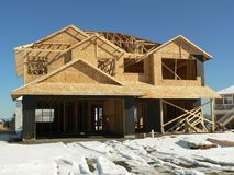 New house. A partially clad house under construction stock photography