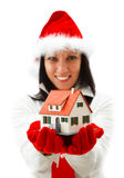 New house for Christmas. Sexy Christmas woman offering a toy house to us Royalty Free Stock Image