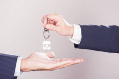 New house concept. Two hands and a key. New house concept Royalty Free Stock Photography