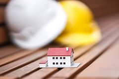New house construction concept. Protective hardhats and a house scale model. Selective focus royalty free stock images
