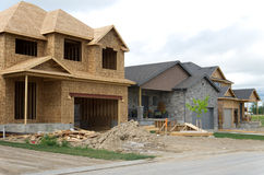 New House Construction. View of a street with new houses under construction next to a recently completed one Royalty Free Stock Image