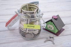 New house for the family and money coins in the jar, saving money on real estate to buy a new home royalty free stock images