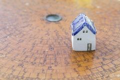 Ceramic miniature house on ancient wooden feng shui compass background stock image